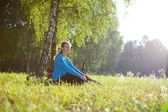 Woman cyclist enjoying relaxation in spring sunny park — Stock fotografie