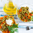 Salad with canned peas, boiled carrots and bottle oil on fabric — Stock Photo