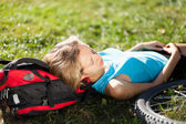 Young girl cyclist enjoying relaxation lying in the fresh grass — Stock Photo