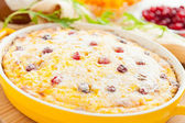 Curd pudding with cranberries and raisins close-up in dish — Stock Photo