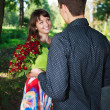 Young mgives girl bouquet of red roses in summer park — Stock Photo #19185381
