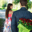 Young man keeps behind his back a bouquet of red roses gift a hi — Stock Photo