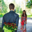 Romantic young man giving a bouquet of red roses to his girlfrie — Stock Photo #19185669