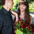 Portrait cheerful young couple with a bouquet of red roses — Stock Photo