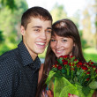 Portrait laughing lovers young couple with bouquet of red rose — Stock Photo #19185881