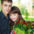 Portrait beautiful lovers young couple with bouquet of red ros — Stock Photo #19185921