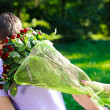 Young man gets hit in the face bouquet of red roses — Stock Photo