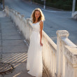 Young woman bride in a white dress in the city in the morning — Foto de Stock