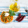 Salad with canned peas and carrots. Oil and hot peppers — Stock Photo