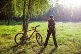 Excited girl cyclist standing in a spring park with hands outstr — Stock Photo