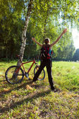 Excited young cyclist standing in a spring park with hands outst — Stock Photo