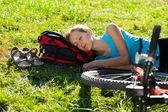 Ung flicka cyklist njuter sover koppla av liggande i den färska gras — Stockfoto
