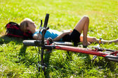 Young girl cyclist enjoying relaxation lying in the fresh green — Stock Photo