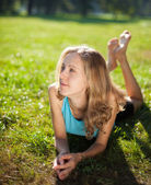 Young girl enjoying relaxation lying in the fresh green grass — Stock Photo