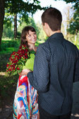 Young man gives a girl a bouquet of red roses in a summer park — Stock Photo