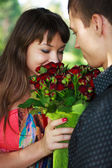 Young woman enjoys the smell given of a bouquet of roses — Stock Photo