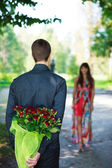 Romantic young man giving a bouquet of red roses to his girlfrie — Stock Photo