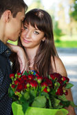 Portrait lovers beautiful young couple with a bouquet of red ros — Stock Photo