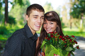 Portrait laughing lovers young couple with a bouquet of red rose — Stock Photo