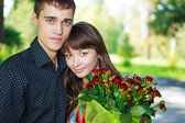 Portrait beautiful lovers young couple with a bouquet of red ros — Stock Photo