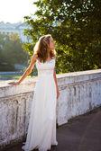 Young girl bride in a white dress near to white old concrete fen — Stockfoto