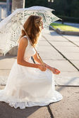 Beautiful girl bride with decorative umbrella in the sunny morni — Stock Photo