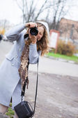 Beautiful girl press photographer or tourist shooting looking at — Stock Photo