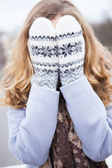 Girl in winter clothes covered her face with wool mittens — Stock Photo