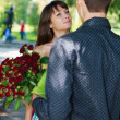 Young man gift a woman a bouquet of red roses in a summer park — Stock Photo