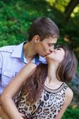 In love couple kiss in a summer green park — Stock Photo