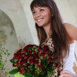 Beautiful smiling womwith bouquet of red roses — Stock Photo #21998923