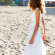 Girl bride in a white dress on the sunny beach half-turned to us — Stok fotoğraf