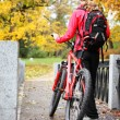 Royalty-Free Stock Photo: Woman cyclist with bike and backpack in autumn park