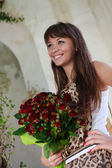 Beautiful smiling woman with a bouquet of red roses — Stock Photo