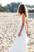 Girl bride in a white dress on the sunny beach half-turned to us — Stock Photo