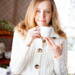 Stock Photo: Smiling young woman with a cup of coffee in hand