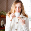 Smiling girl with a cup of coffee in hand — Stock Photo