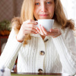 Stock Photo: Smiling beautiful girl with a cup of coffee in hand