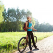 Stock Photo: Womcyclist on walking with bicycle in spring nature
