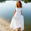 Young cheerful girl bride walk barefoot the sunny coast of the river — Stock Photo #23848531