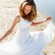 Elegant young girl bride in a white dress on a sandy river beach — Stock Photo
