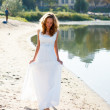 Young girl bride walk barefoot the sunny coast of the river — Stock Photo