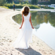 Young girl bride walk sunny coast of river — Stock Photo #23848653