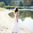 Young girl bride in white dress on sunny coast of river — Stock Photo #23848669