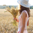 Young girl in the hat and pink dress holding wheat ears in her hand - Stock Photo
