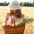 Beautiful woman in the hat with basket full of ripe ears — Stock Photo