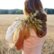 Young woman in pink dress holding wheat ears and hat in her hands — Stock Photo