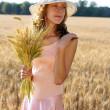 Beautiful woman in the hat holding wheat ears in her hand — Stock Photo