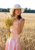 小麦の穂彼女の手で保持している帽子の美しい女性 — ストック写真