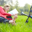 Stock Photo: Girl cyclist on halt reads lying in fresh green grass barefoot